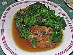 Roast duck hidden under leafy greens