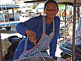 Vendor frying chicken at the market, Takua Pa
